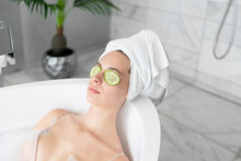 Woman In Towel On Head With Cucumbers Slices On Eyes Lying In Foam Bath. Caring Natural Organic Facial Mask. Spa Relaxing And Rest In Bubble Bathtub. Skin Beauty Procedure And Health Care