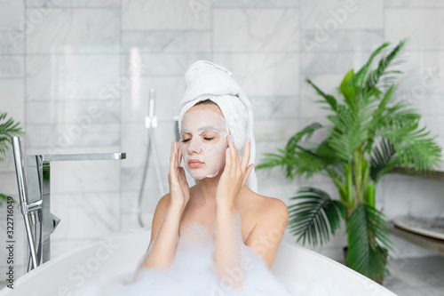 Cuadros en Lienzo Young woman applying cosmetic face sheet mask while taking bath