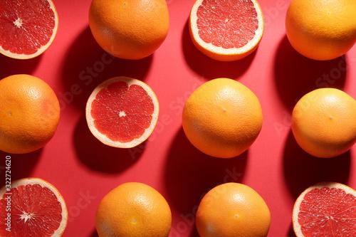 Fototapeta Cut and whole ripe grapefruits on red background, flat lay