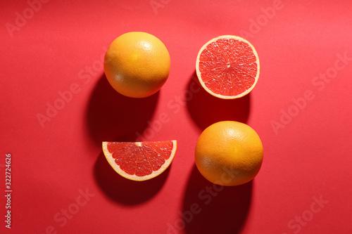Obraz na plátně Cut and whole ripe grapefruits on red background, flat lay