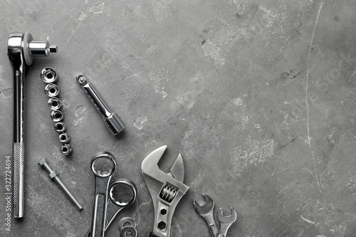 Fototapeta Auto mechanic's tools on grey stone table, flat lay. Space for text obraz