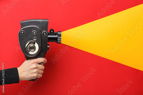 Female hand holding old style film movie camera imitating shooting process on a Tablou Canvas