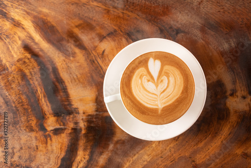 Photo Coffee cup latte art in heart shape with a cup of dark coffee and dark chocolate on wooden table