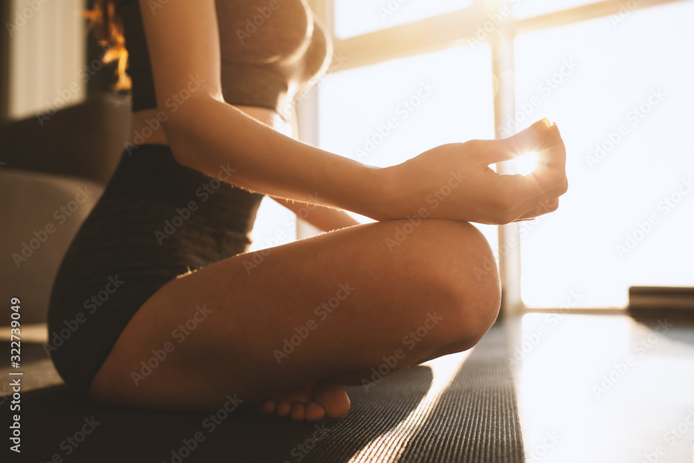 Fototapeta Young girl relaxing in yoga position in front of a bright window