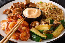 Hibachi Dish Consisting Of Fried Rice With Egg, Shrimp, Steak And Vegetables Served With Sauce Closeup In A Plate. Horizontal