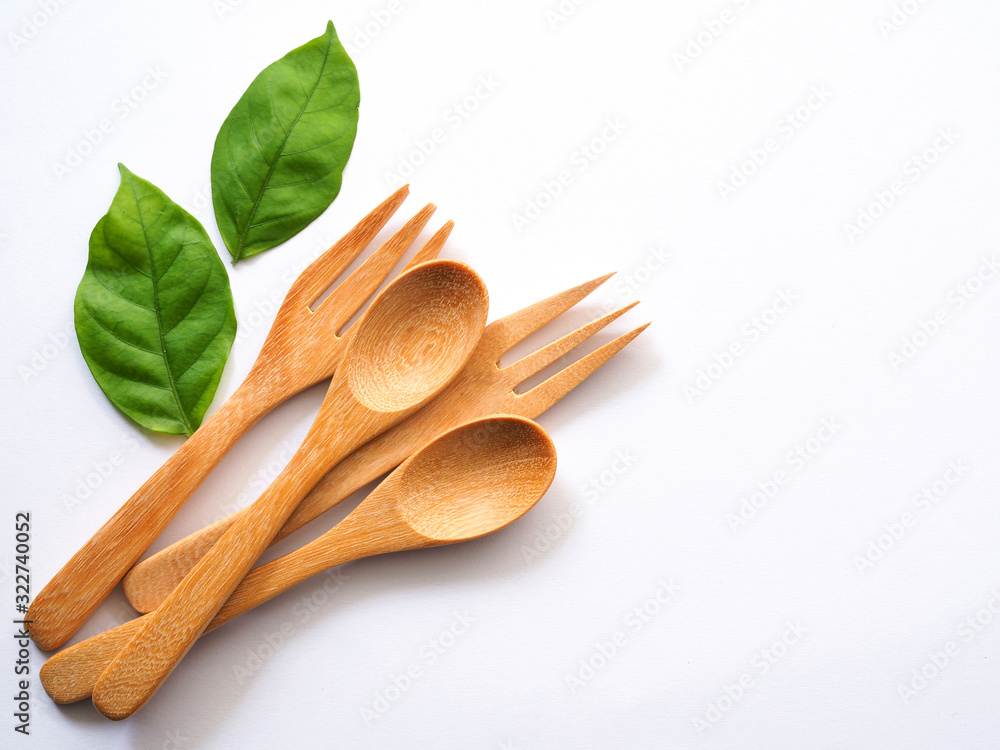 Fototapeta Wooden spoon and fork and green leaves, Natural wooden utensils Eco-friendly And safe for health With copy space for text of design.