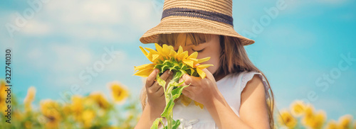 Obraz A child in a field of sunflowers. Selective focus. - fototapety do salonu
