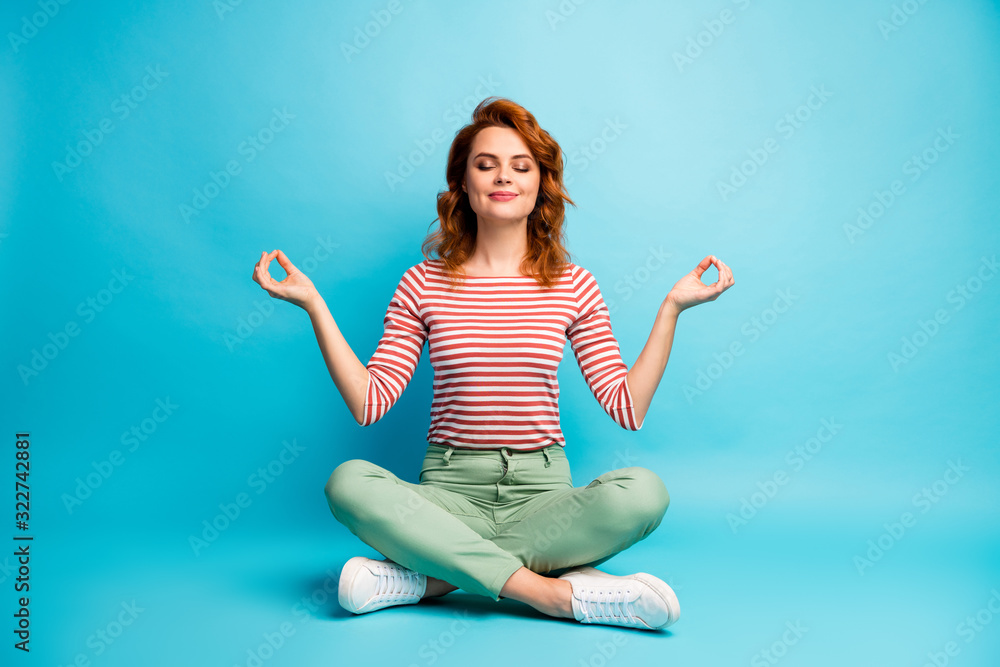 Fototapeta Full size photo of quiet serene woman sit floor crossed legs show om sign exercise yoga meditation wear stylish green outfit isolated over blue color background