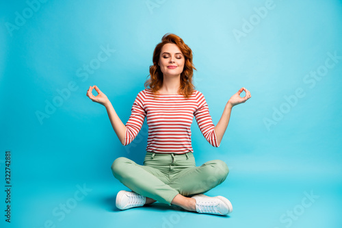 Full size photo of quiet serene woman sit floor crossed legs show om sign exercise yoga meditation wear stylish green outfit isolated over blue color background