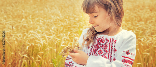Fotomural A child in a field of wheat in an embroidered shirt