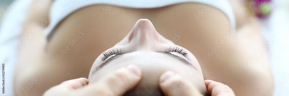 Fototapeta Male masseur hand make face massage young caucasian woman against spa cabinet background portrait. Beauty wellness concept