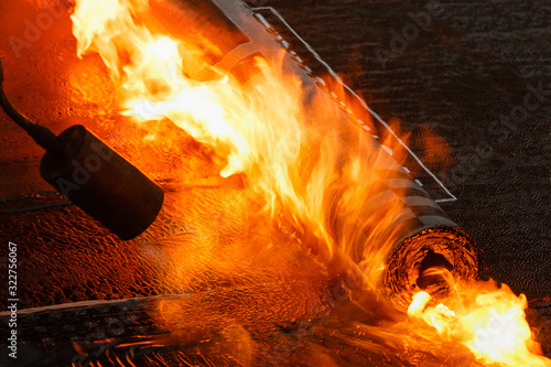 Laying of roofing felt from the roll with a flame from the burner close-up Canvas Print