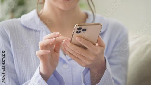 Obraz スマートフォンを操作している女性 - fototapety do salonu