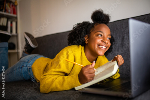 Carta da parati happy african american girl student looking at laptop computer screen at home