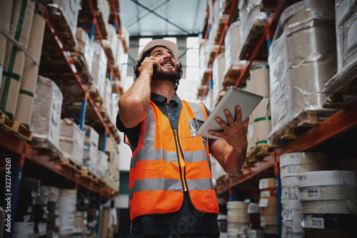 Fotografía Low angle view of warehouse manager talking over phone while smiling and holding