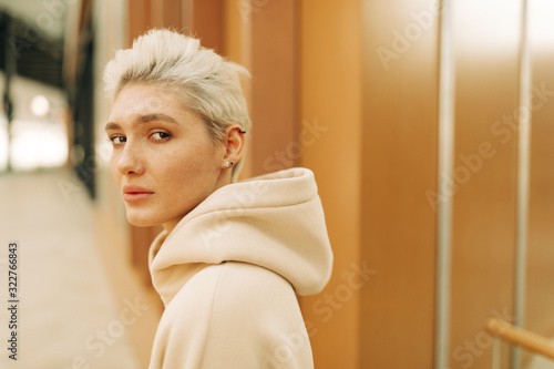 Young woman in pale hoody on the street #322766843