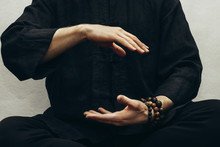 A Man In Black Shirt Sitting And Doing Qigong. Hands Direct Energy. Prayer, Gratitude.Practicing Monk. Qi Energy. Yoga Pose. Close Up