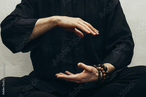 Fotografering A man in black shirt sitting and doing qigong