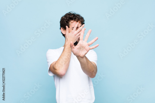 Slika na platnu young crazy bearded man covering face with hand and putting other hand up front