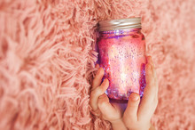 Sparkle Magic Electric Pink Jar With LED Bulbs Inside And A Silver Closed Lid On A Fluffy, High-pile Pink Blanket.