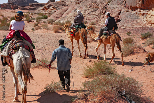 Photo Some tourists on camels accompanied by Bedouins in the panorama of the Jordanian desert of Wadi Rum