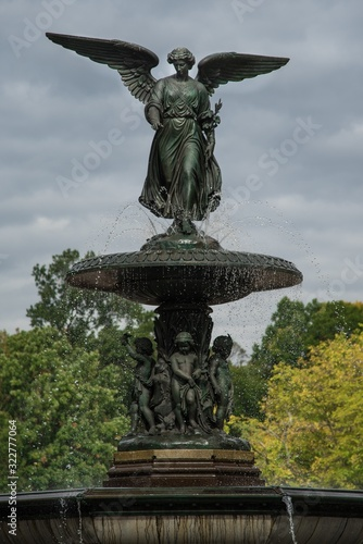 фотография Vertical shot of bethesda fountain in new york city, USA with a gloomy sky in th