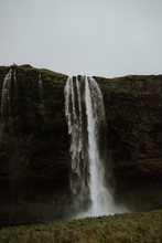 Beautiful Scenery Of A Powerful Waterfall Near High Rocky Cliffs