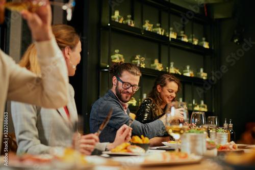 Fototapety, obrazy: Group of best friends sitting in restaurant, having dinner, drinking wine and having fun.