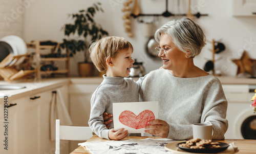 Fototapeta happy family grandson child congratulates grandmother on holiday and gives card obraz