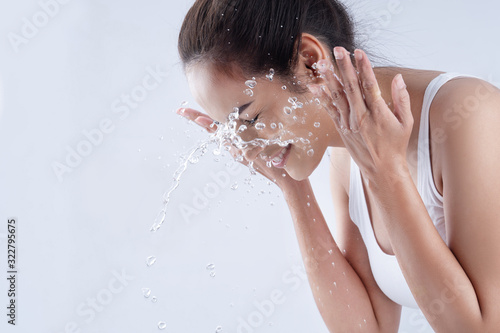 Fotografiet Beautiful woman washing her face in a white background studio