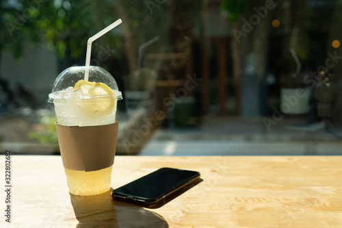 Iced italian lemon soda in clear plastic glass with black smart phone on the wooden table in the cofee shop what has window with garden view