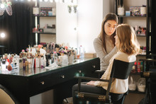 Beautiful Female Makeup Artist Doing Makeup For A Young Blond Hair Girl In A Beauty Salon Sitting In Front Of A Large Mirror. Concept Of Preparation For The Holiday And Meeting. Start Working