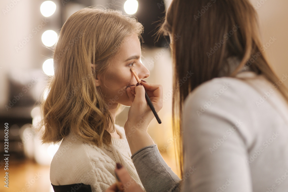 Fototapeta Makeup artist work in her beauty studio. Portrait of Woman applying by professional make up master. Beautiful make up artist start making a makeup for blond hair model