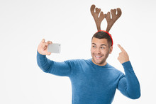 Portrait Of Funny Crazy Man In Deer Horns Making Selfie On Christmas Event Isolated Over White Color Background