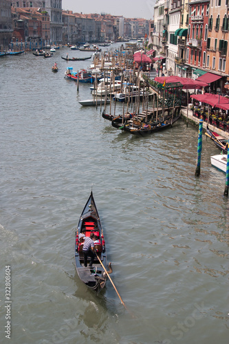 Foto view of Venice showing a gondola in the foreground on the Grand Canal in the hea