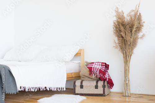 Beach home decor with boho cushions, vase with lavender flowers and old books. Cottage style interior decoration.