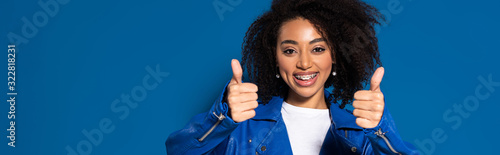 Photo smiling african american woman showing thumbs up on blue background, panoramic s