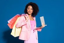 Smiling Elegant African American Businesswoman With Shopping Bags Using Laptop On Blue Background