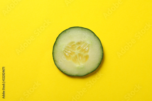 Fototapeta Cucumber slice on yellow background, top view obraz