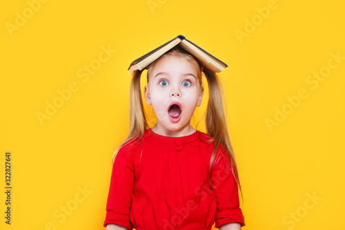 Obraz Shocked little girl holding book on her head and looking at camera - fototapety do salonu