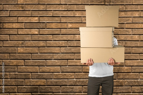 Obraz Delivery man carrying stacked cardboard boxes in front of face - fototapety do salonu