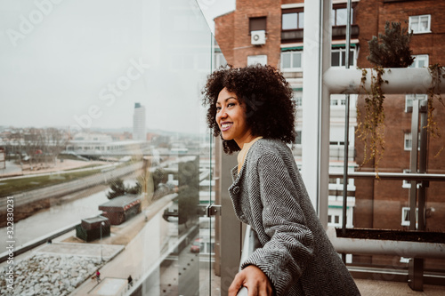 Obraz .Beautiful African American woman looking out the window of a tall building overlooking the city of Madrid. Relaxed and carefree. Lifestyle - fototapety do salonu