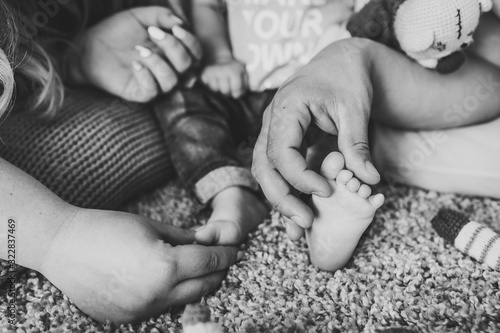 Young parents holding support child's feet with his hand and cute little baby lying on bed at home. Baby feet. Mom and Dad hold son legs. Taking care of a newborn. Close up. Black and white photo.