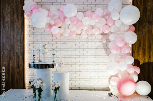 Fotografía Photo-wall, wedding decoration space or place from white and pink balloons and white brick wall near table with a wedding cake, candles and flowers