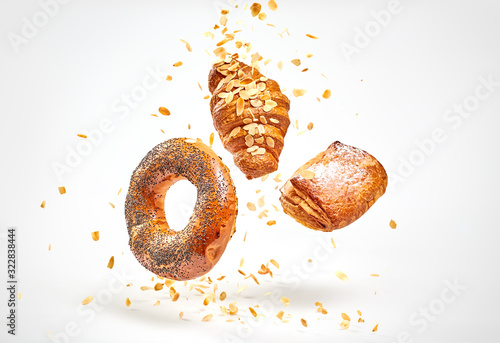 Fototapeta Croissant bun brioche cake flying in air. Fresh baked puff pastry cookie falling on white. Delicious french baking croissant with almond. Levitation, fly bread bakery products cafe concept obraz