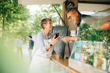 Female Owner Showing Smart Phone To Male Coworker While Standing By Food Truck