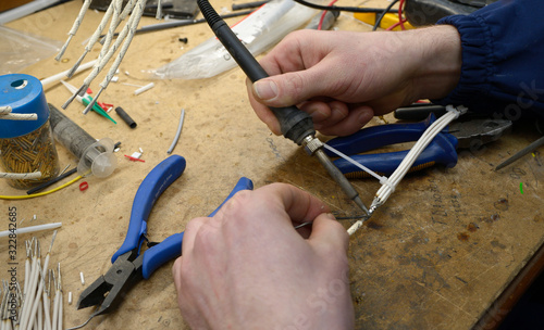 Valokuvatapetti Worker hands solder wires with the soldering iron, pliers, pieces of wires on a