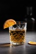 canvas print picture - Vertical shot of a glass of whiskey decorated with a slice of dried orange