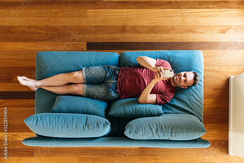 Fototapeta Casual guy on armchair with smartphone