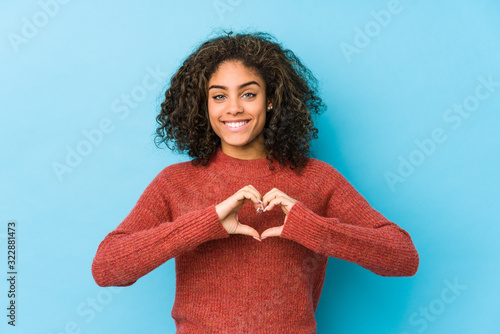 Obraz Young african american curly hair woman smiling and showing a heart shape with hands. - fototapety do salonu